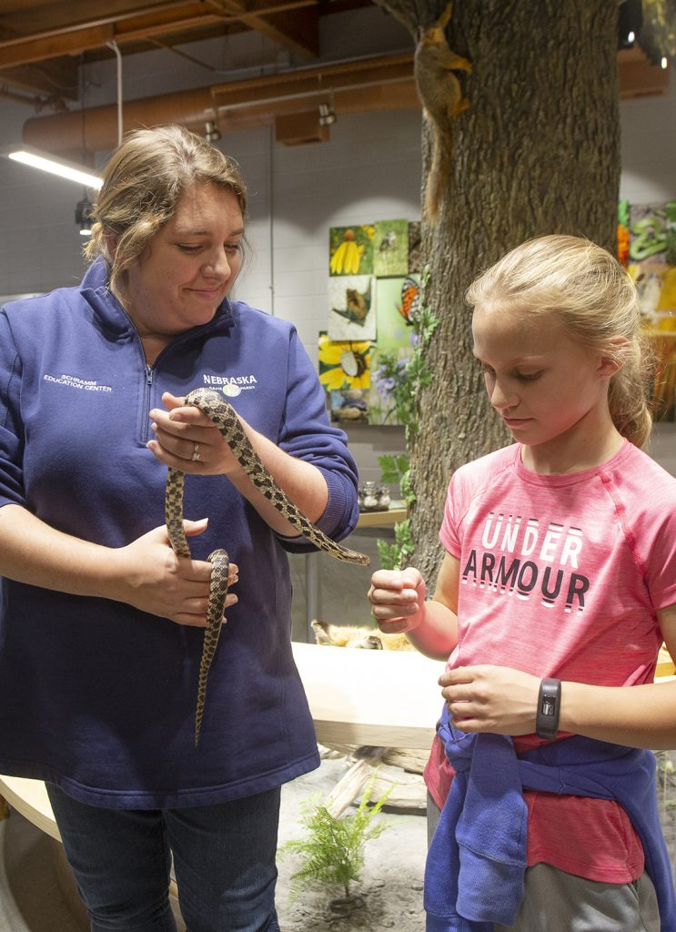 Pictured is the Schramm Education Center (Aksarben Aquarium) in Sarpy County. Naturalist Amber Schiltz teaches Logann Dostal of Gretna about snakes. Kurrus, May 9, 2019. Copyright NEBRASKAland Magazine, Nebraska Game and Parks Commission.